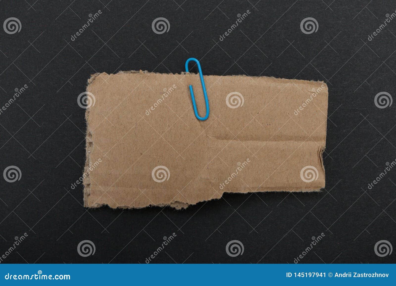 Pappe mit dem Clip lokalisiert auf schwarzem Hintergrund Raum für Ihre Mitteilung, Modell