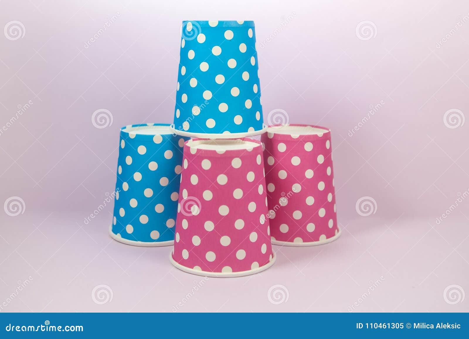 Pappers- kopp för blå och rosa prick på den rosa bakgrunden