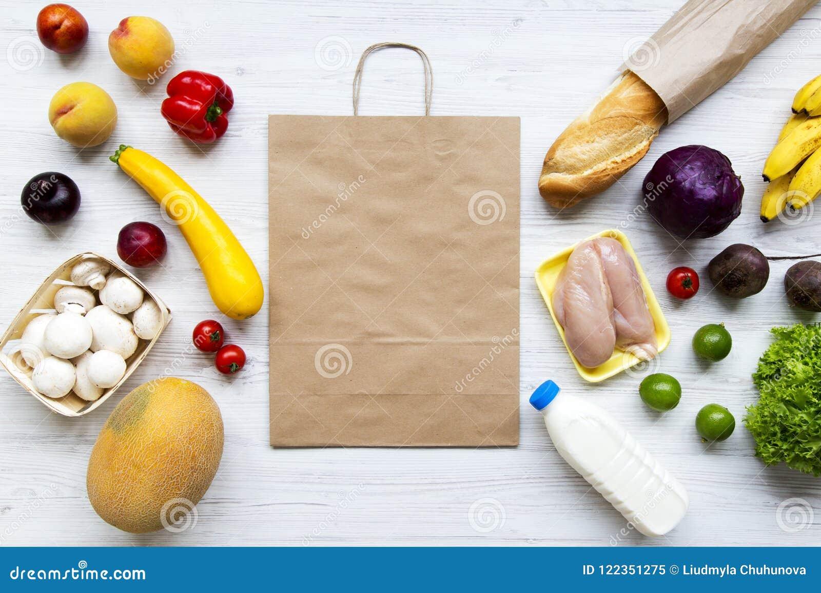 Pappers- påse av sund organisk mat på vit träbakgrund Matlagningmatbakgrund Lägenhet-lekmanna- av nya frukter, veggies, gräsplane