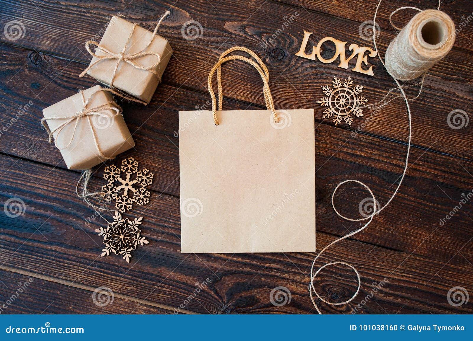 Pappers- påse för modell från askar för kraft papper och julgåvapå en träbakgrund