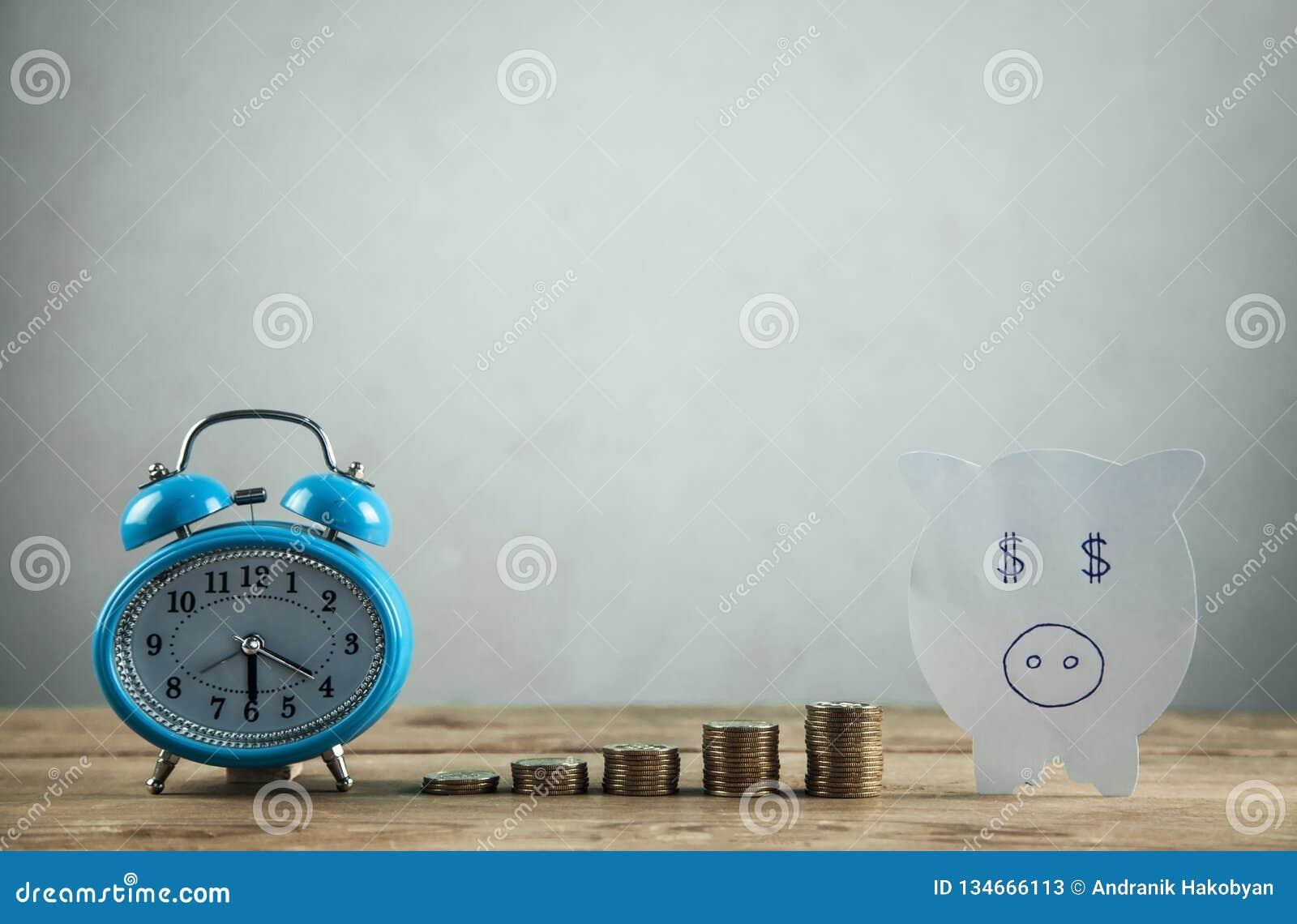 Pappers- spargris, bunt av mynt och ringklocka på trätabellen Tid som investerar dina besparingar