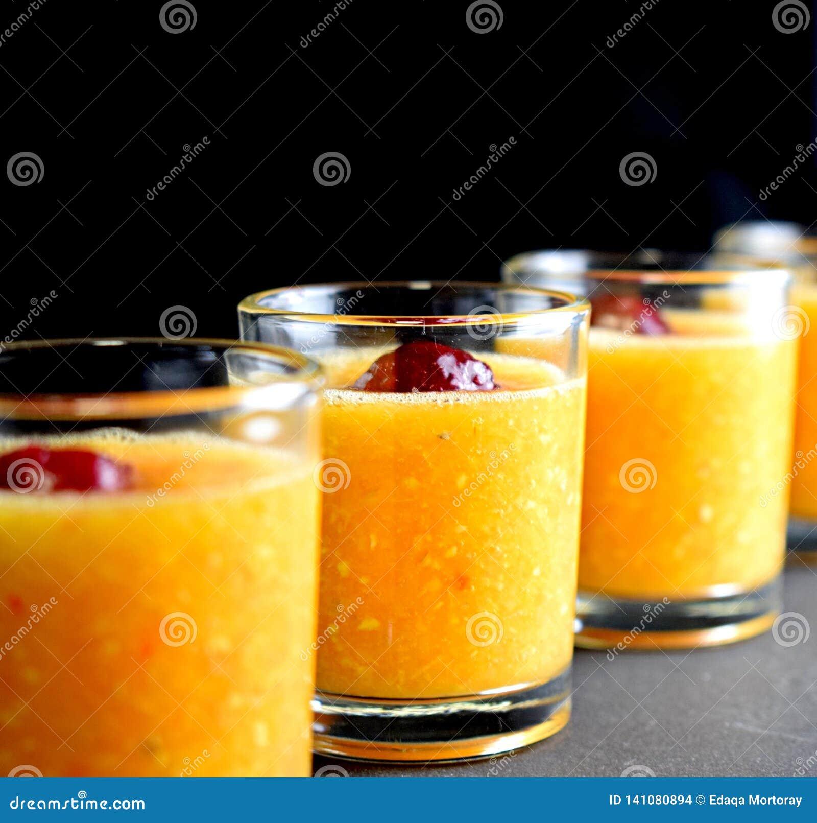 Pappige oranje drank met kers in geschotene glazen