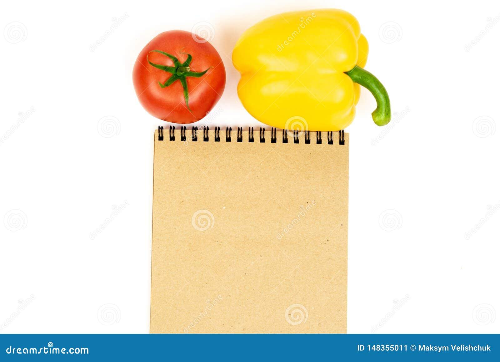 Paprika amarillo con los tomates aislados en el fondo blanco cerca de la libreta Composición de la pimienta amarilla y del tomate