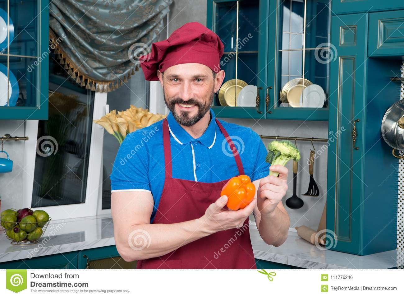 Paprika and broccoli in man hands. Smiled chef with vegetables in his hands. Portrait of bearded guy at kitchen