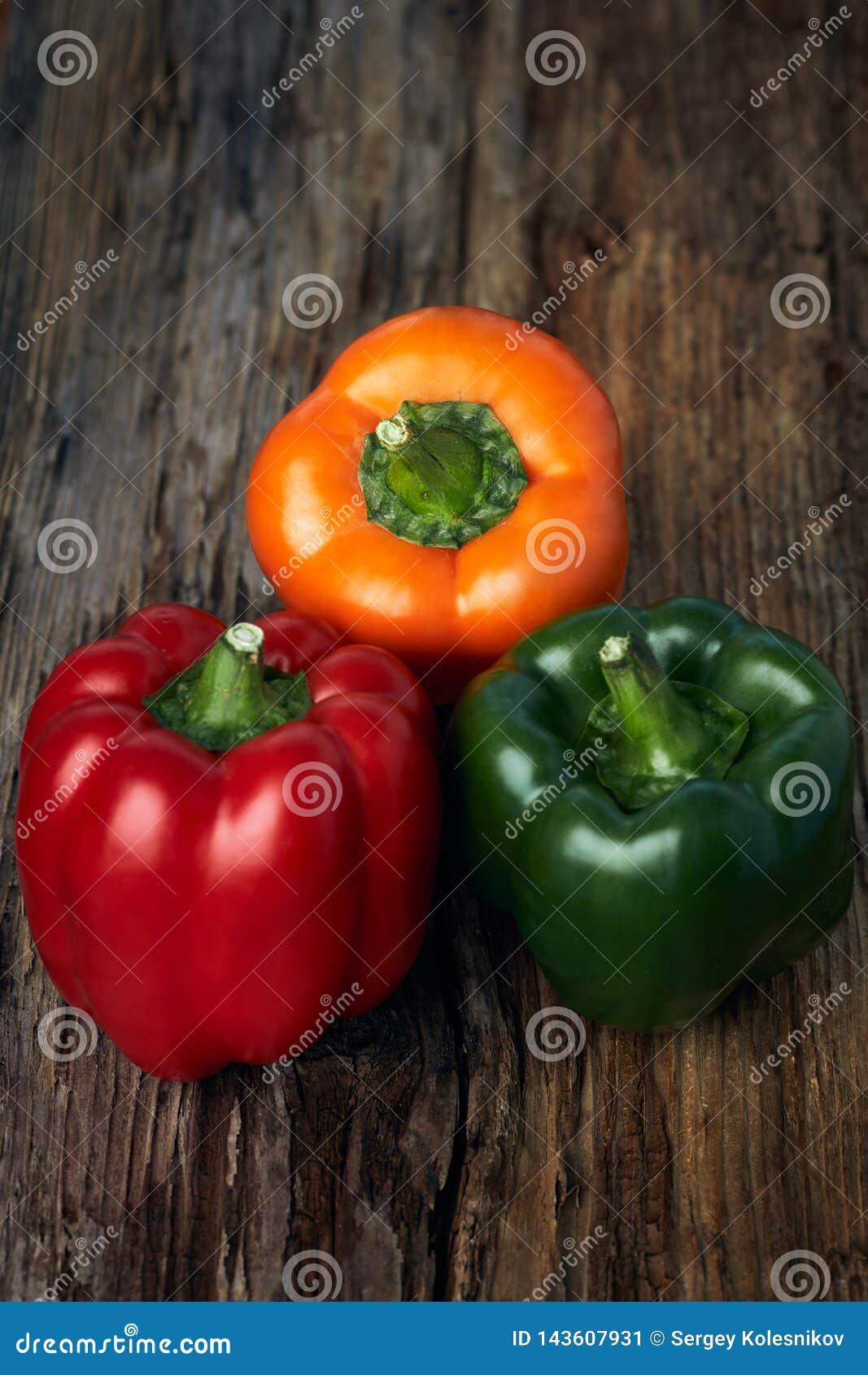 Paprika colorida das pimentas verdes, amarelas, e vermelhas no fundo