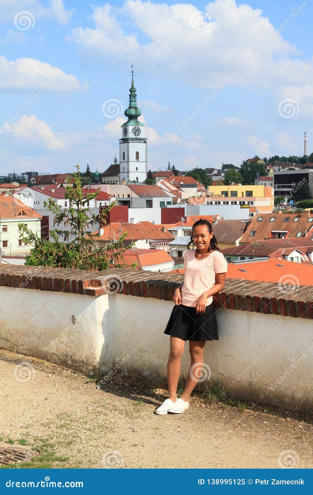 Papuan flicka med stadstornet i Trebic bakom