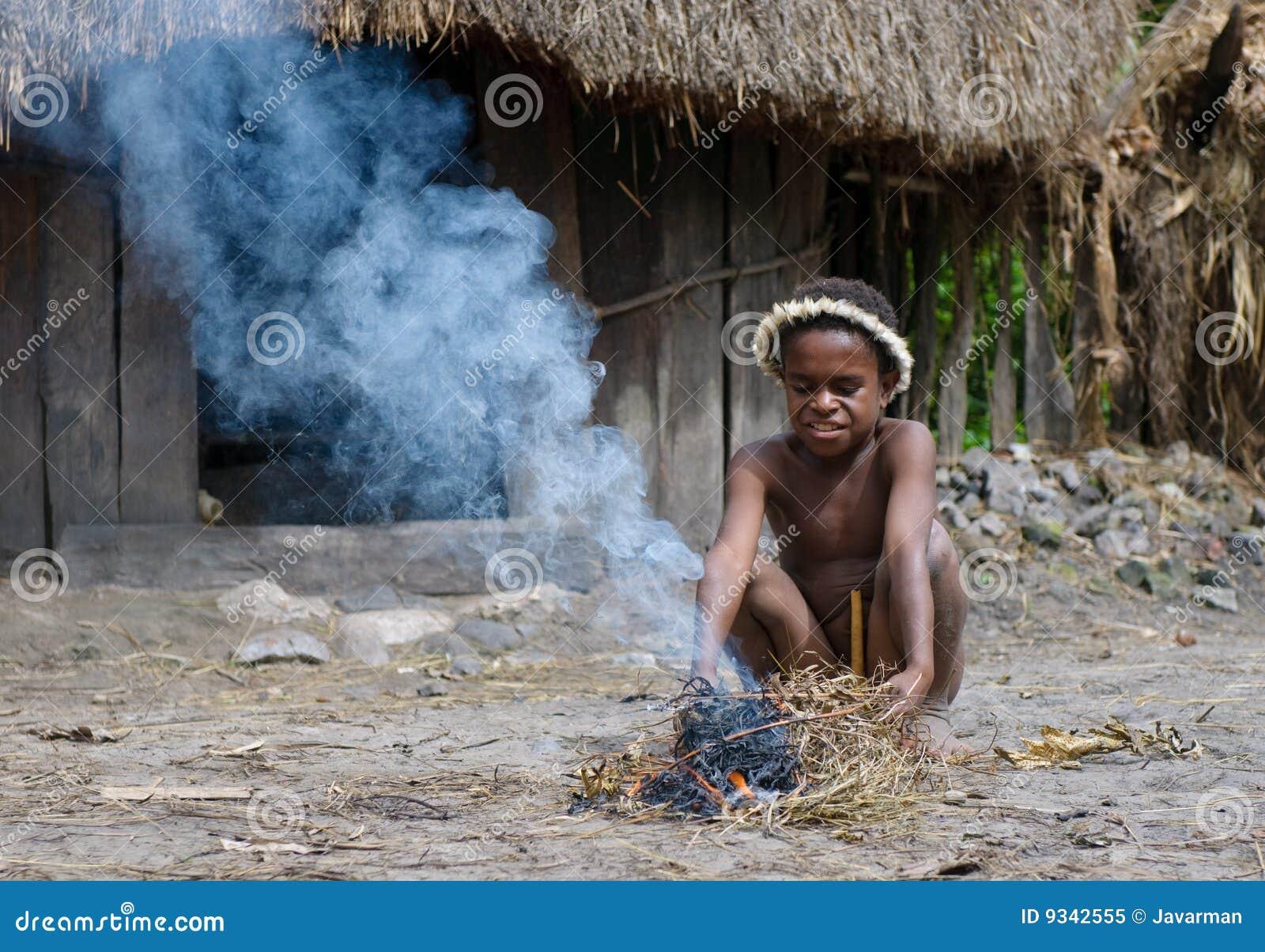 Papuanjunge, der Feuer, Wamena, Papua, Indonesien bildet