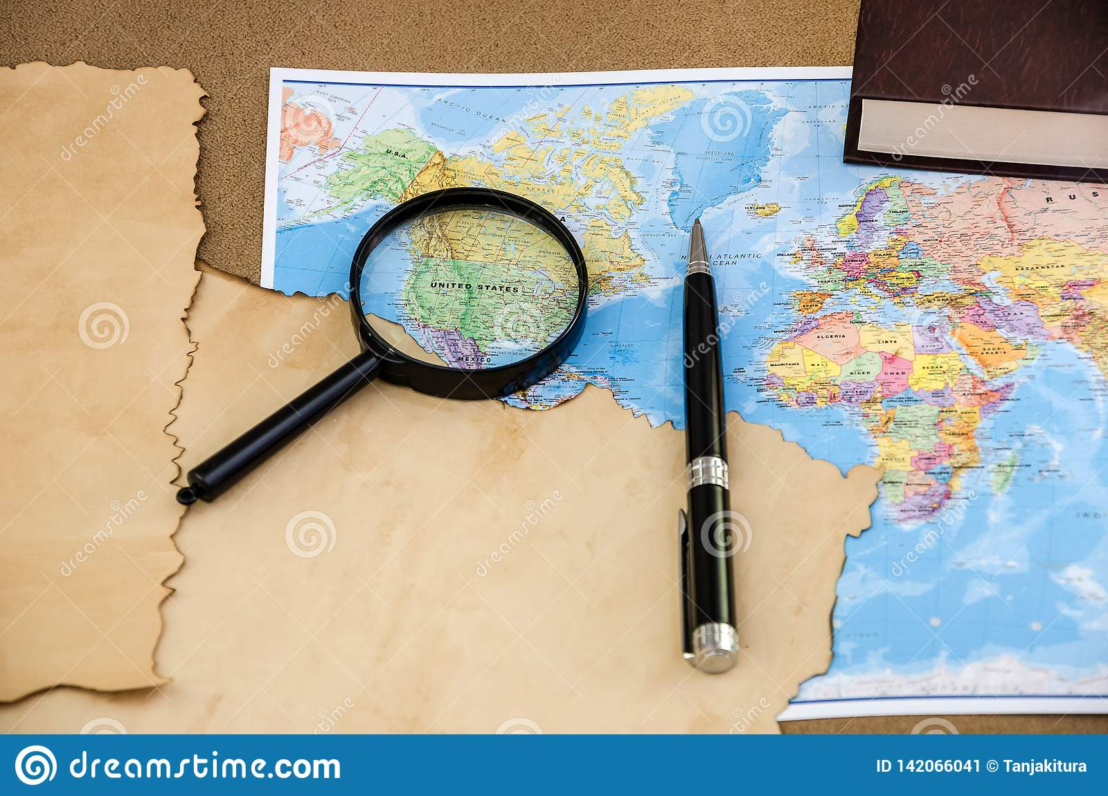 Papyrus on a world map, pen and magnifier