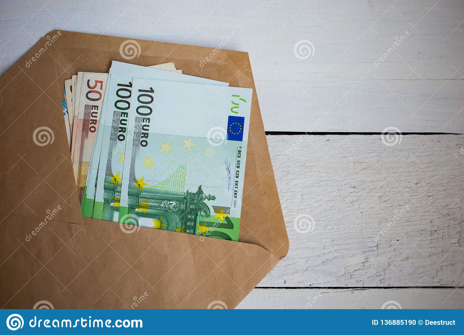Paquete ascendente cercano de billetes de banco de los euros del dinero en sobre en la tabla de madera