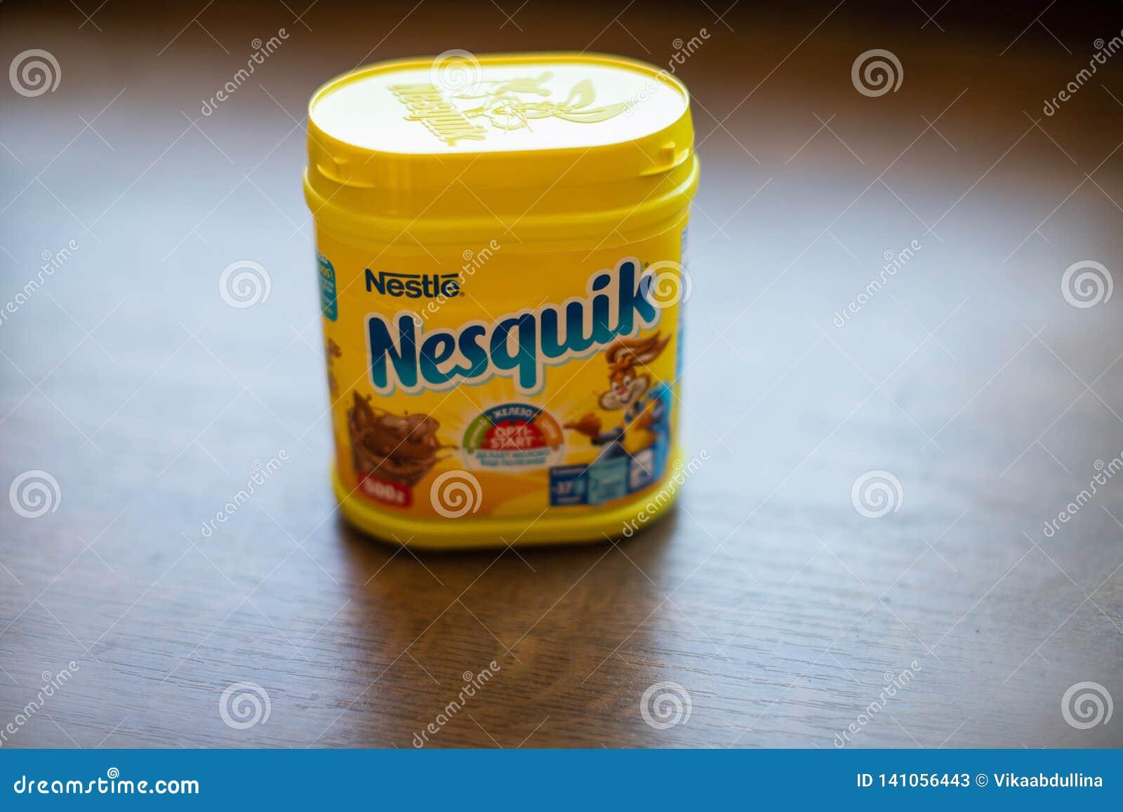 Paquete de la bebida Nesquik del chocolate y del cacao por Nestle en fondo de madera