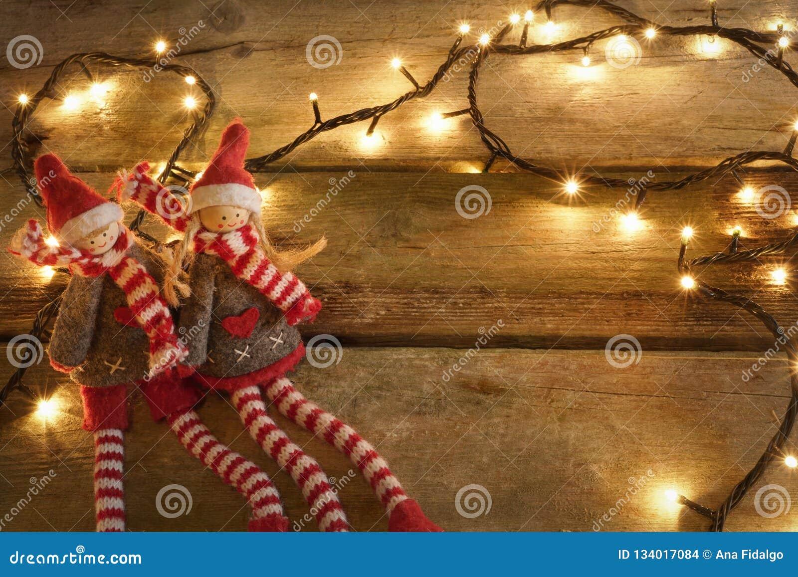 Par av förtjusande och gulliga julälvor som sitter i lantlig trätabell med gula julljus Med kopiera utrymme