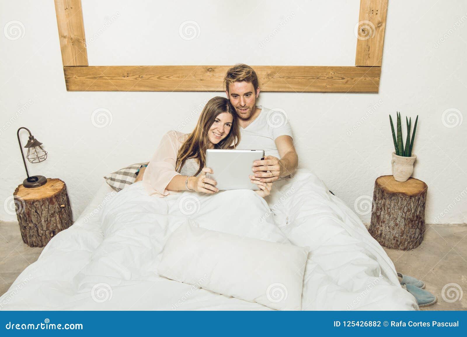 Par av grabben och flickan i säng som håller ögonen på en minnestavla