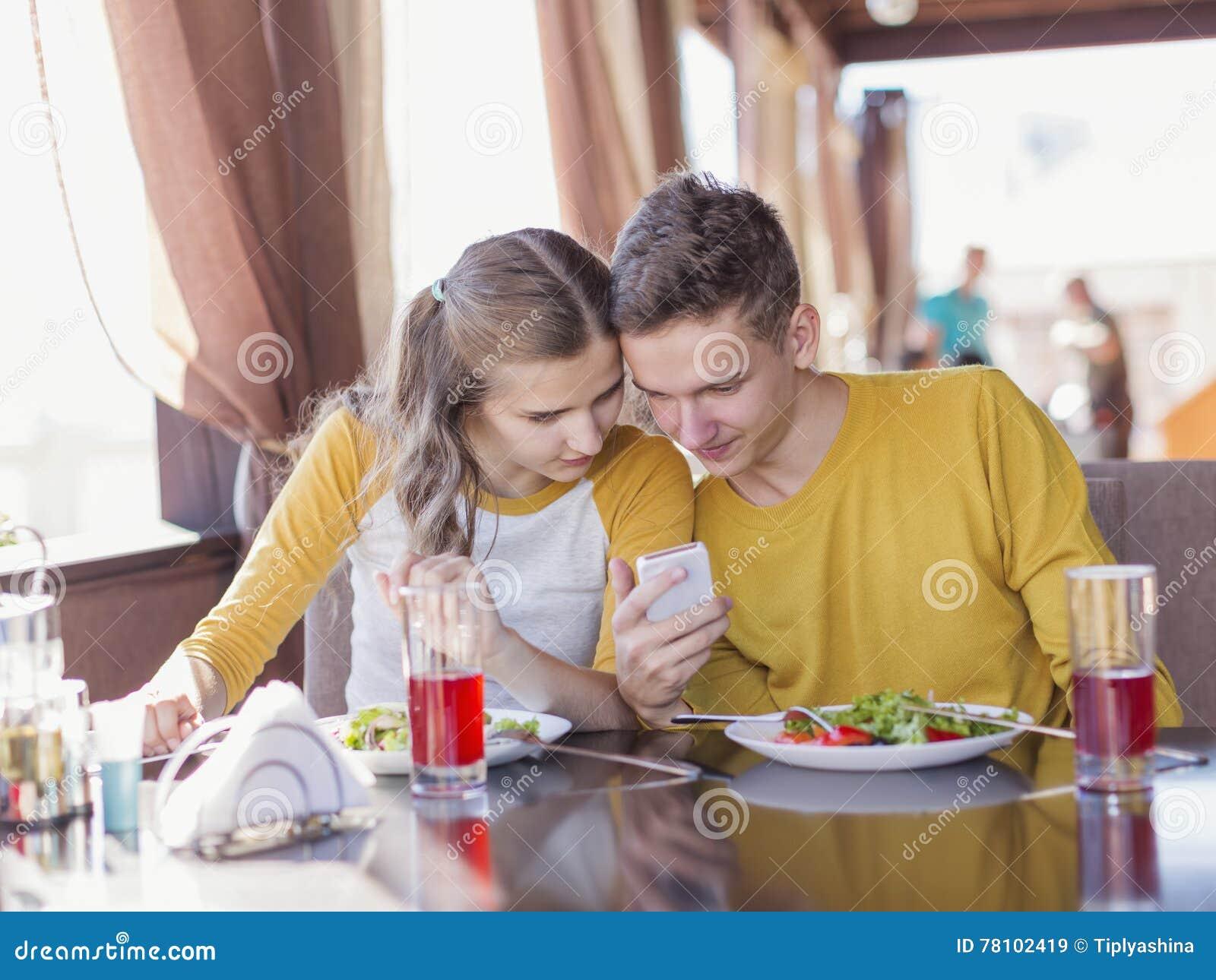 Par av tonåringar i ett sommarkafé