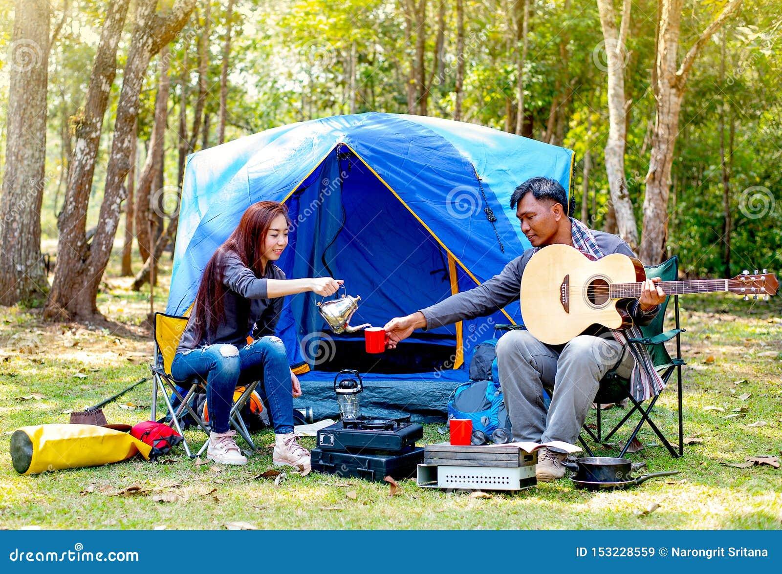 Par av vännen campar nära skogen har att koppla av aktivitet med manlekgitarren, och kvinnan ger honom med en kopp kaffe