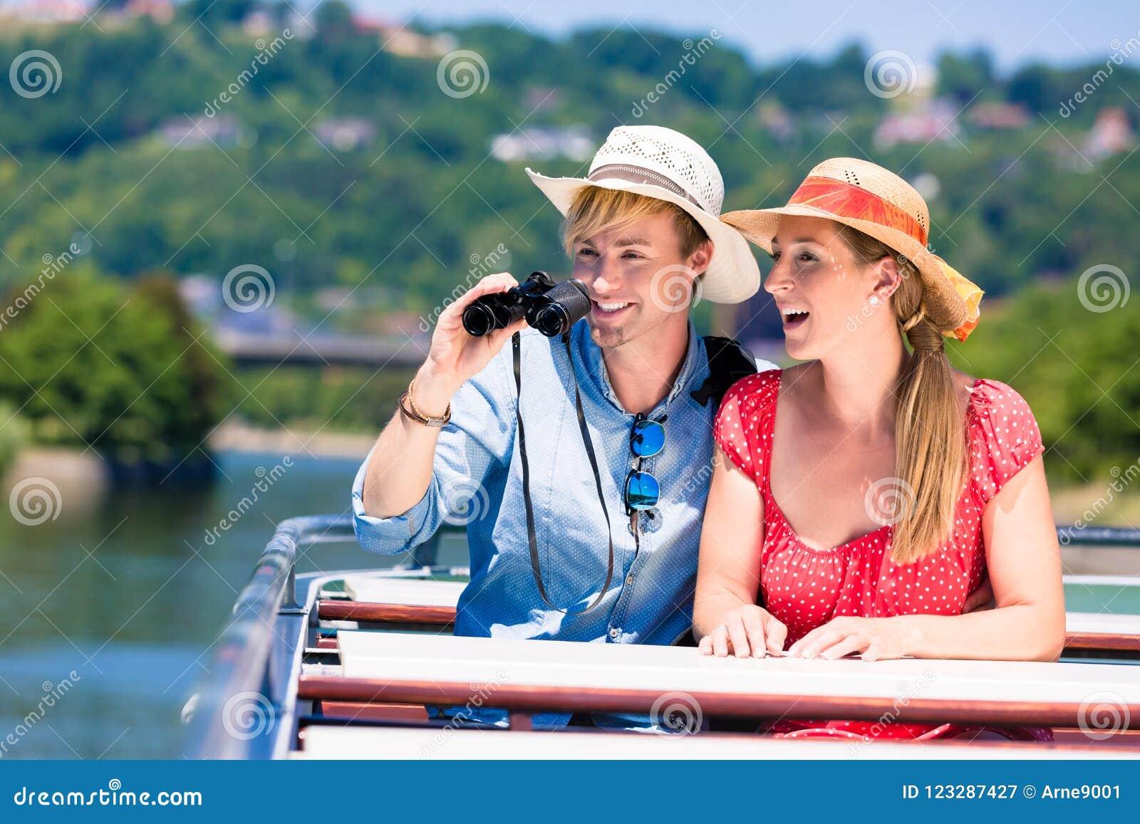 Par på floden kryssar omkring bärande solhattar i sommar
