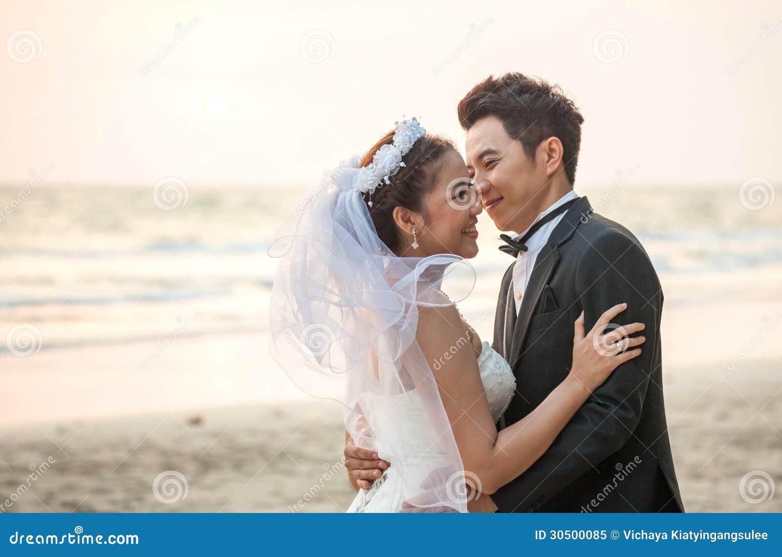 Par som gifta sig strandsolnedgång