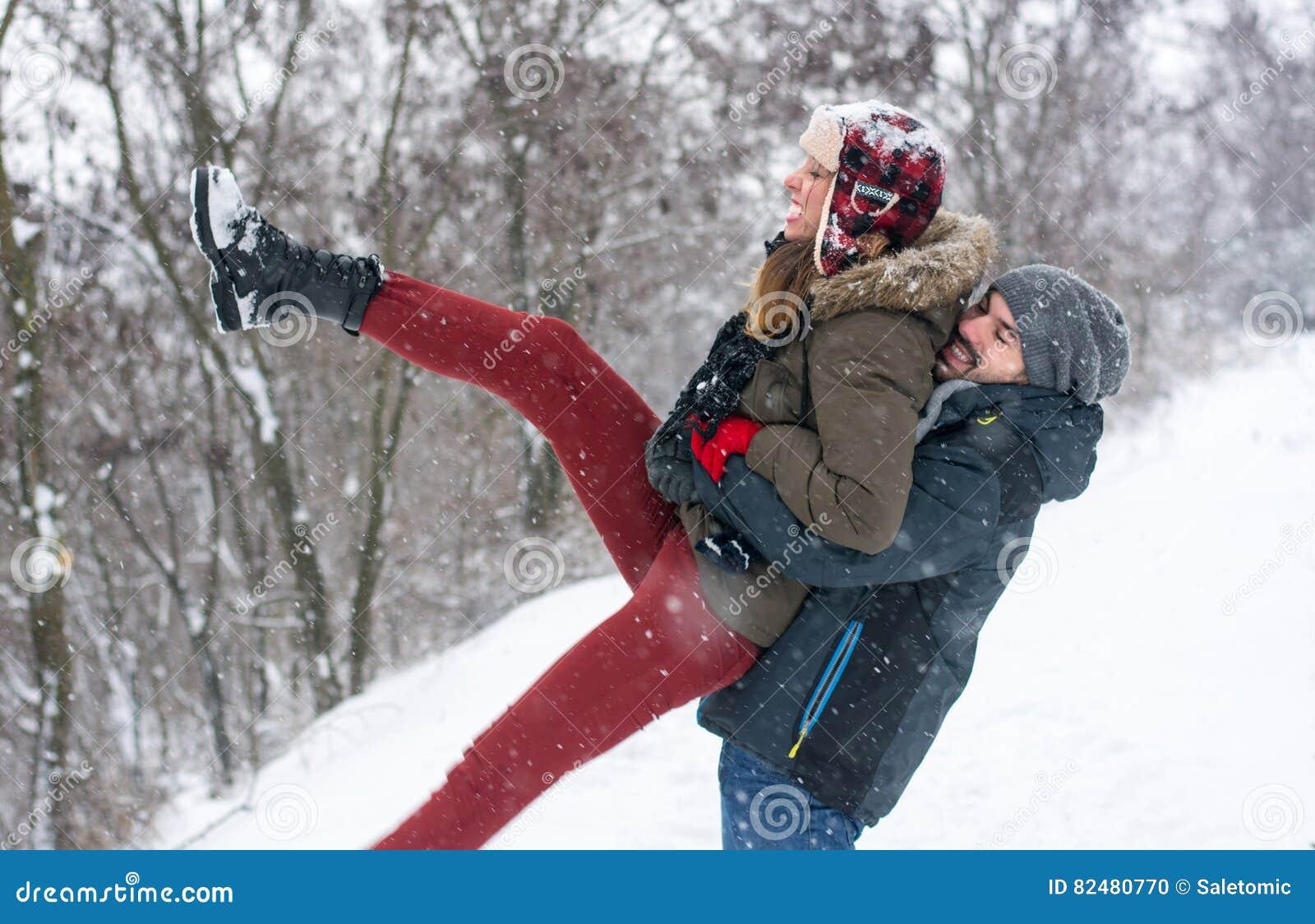 Par som har gyckel i täckt snö, parkerar