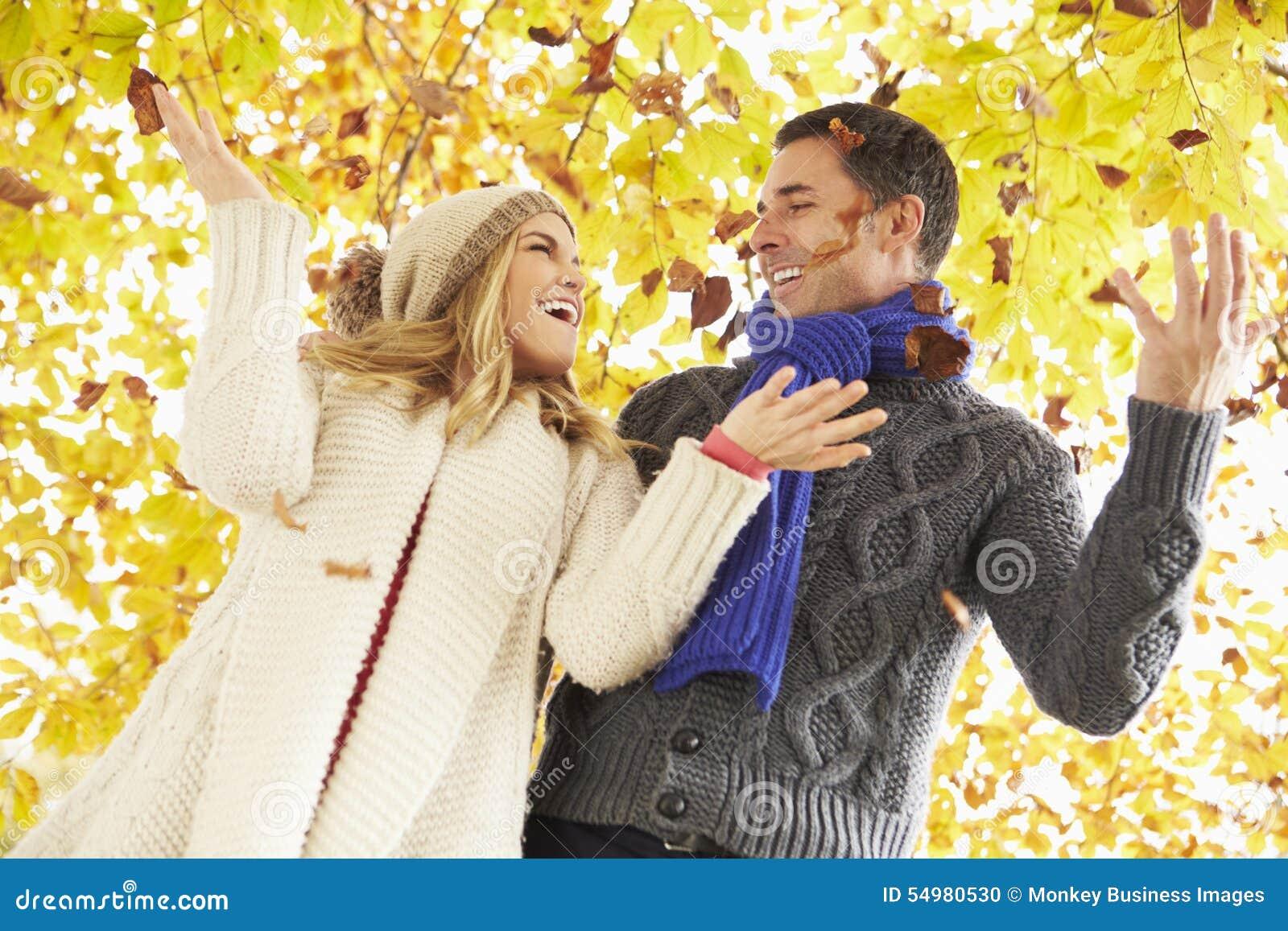 Par som kastar sidor i Autumn Garden