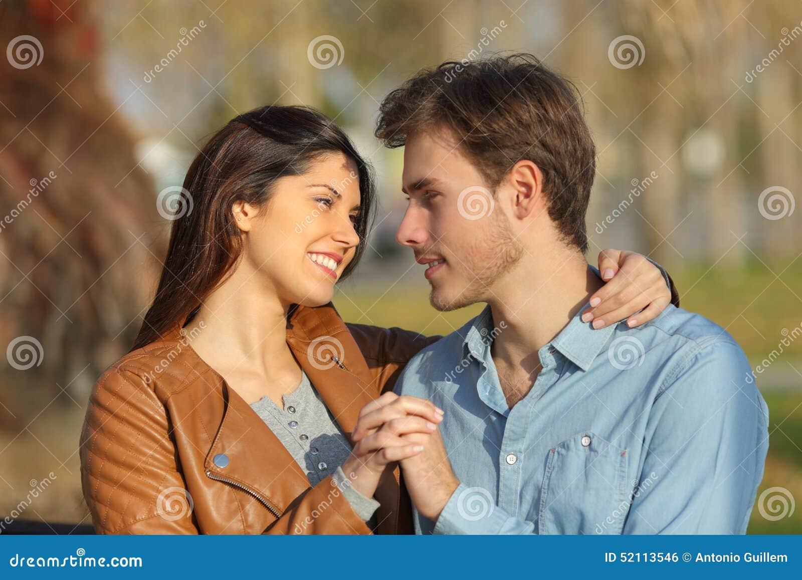 Par som kramar och daterar i en parkera som ser sig