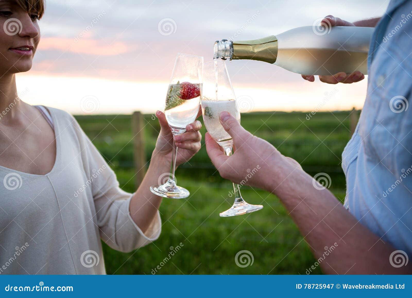 Par som rostar champagne i fält