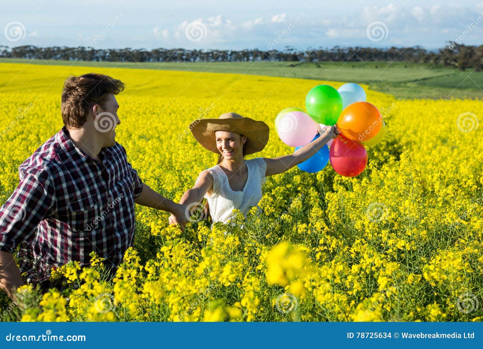 Par som rymmer färgrika ballonger i senapsgult fält