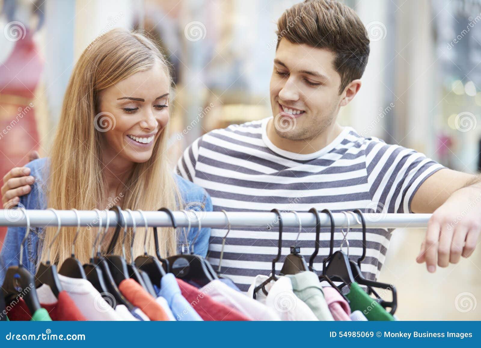 Par som ser kläder på stången i shoppinggalleria
