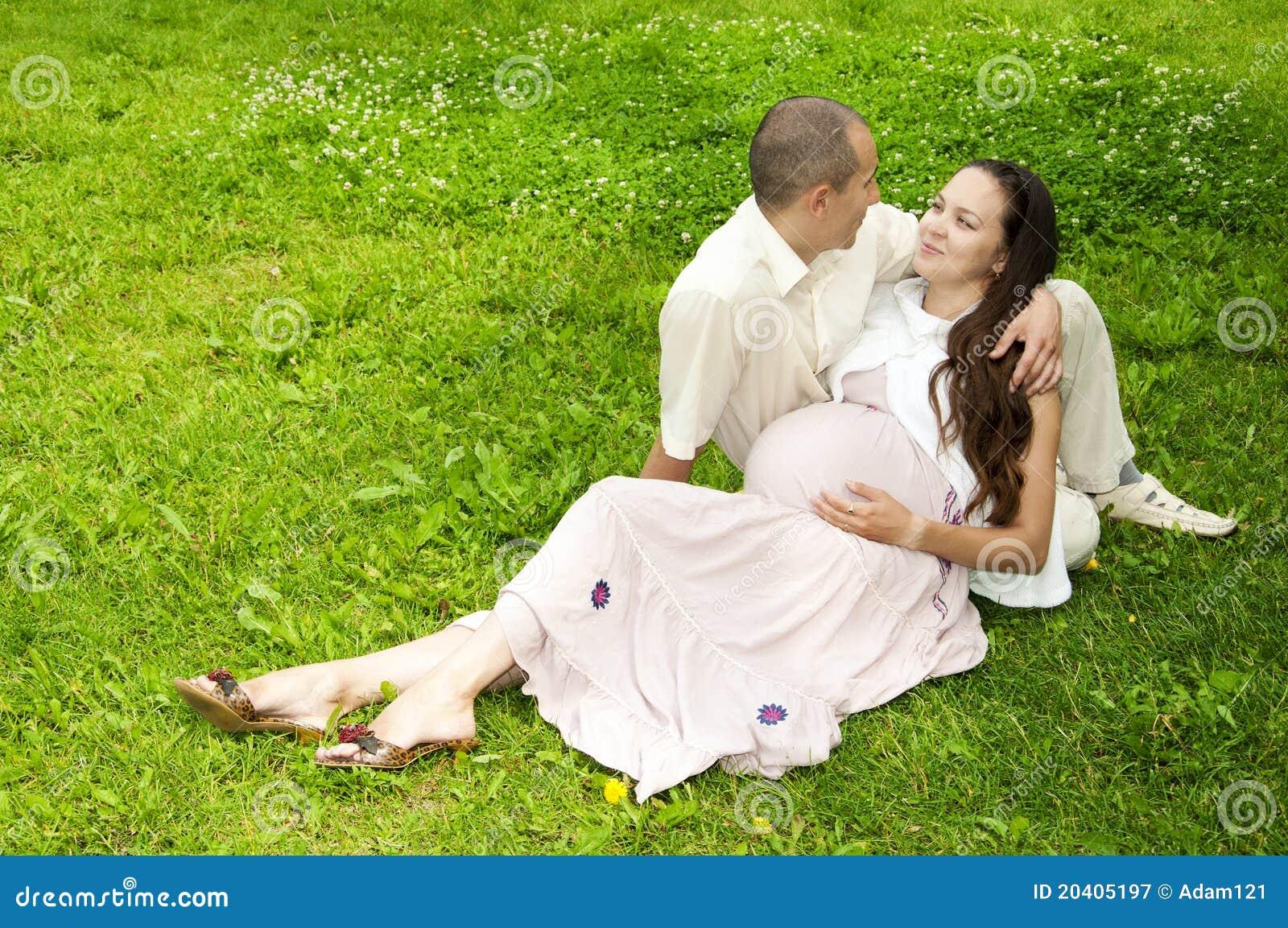 Par som tillsammans kramar den gravida kvinnan för lays