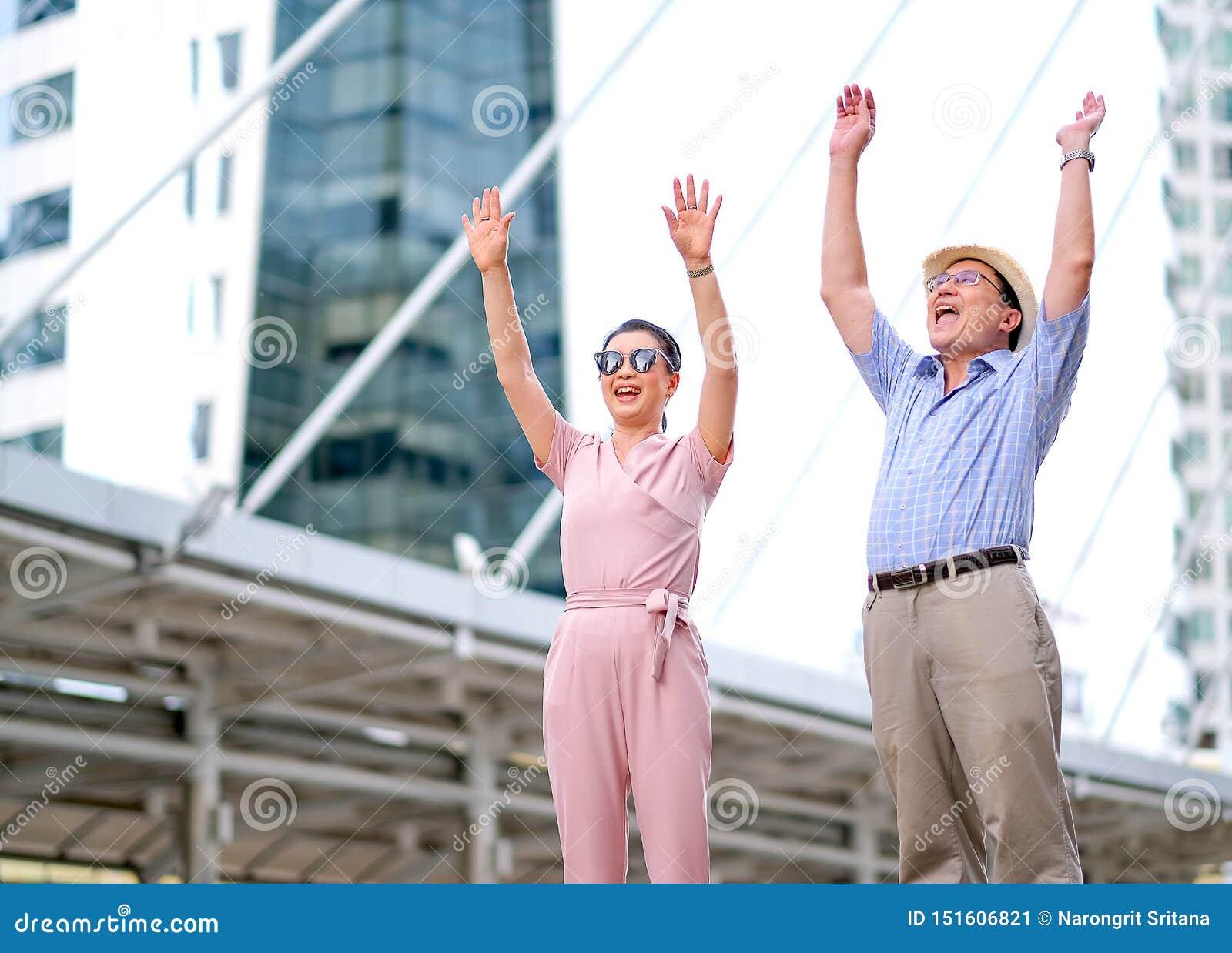 Para Azjatycki starego człowieka i kobiety turysta postępuje jak podniecający i bardzo szczęśliwy Ten fotografia także zawiera po