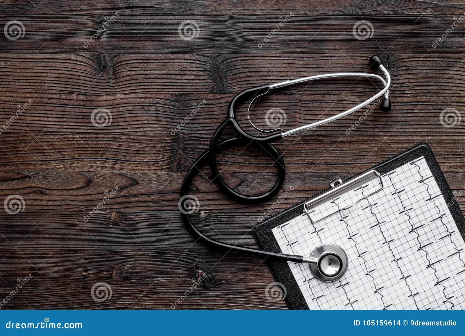 Para diagnosticar enfermedad cardíaca Cardiograma, estetoscopio en copyspace de madera oscuro de la opinión superior del fondo