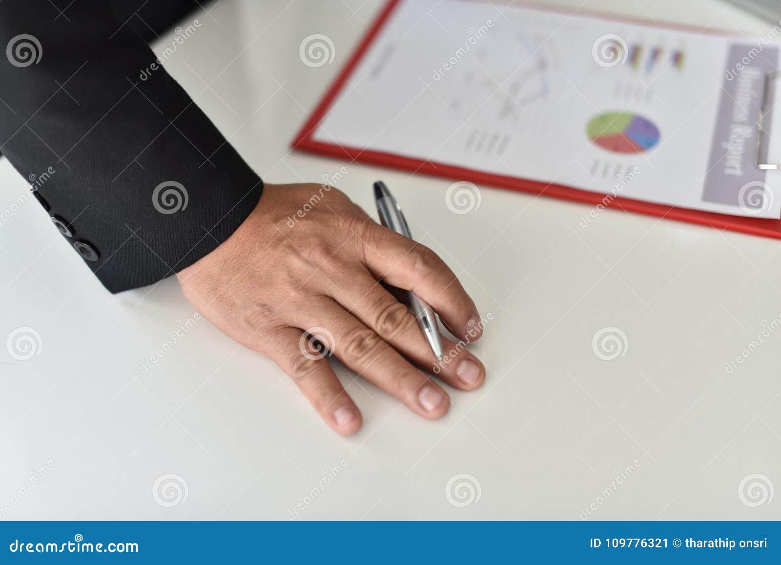 Para firmar, reciba y apruebe Mano del hombre de negocios que señala a la información del gráfico