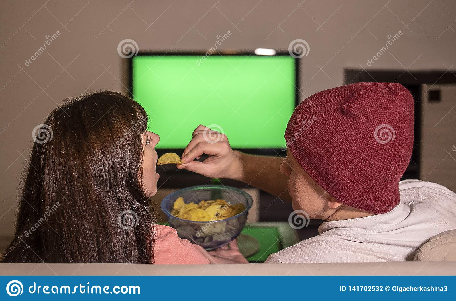 Para małżeńska siedzi w domu na kanapie w wieczór, dopatrywaniu TV i łasowanie układach scalonych,