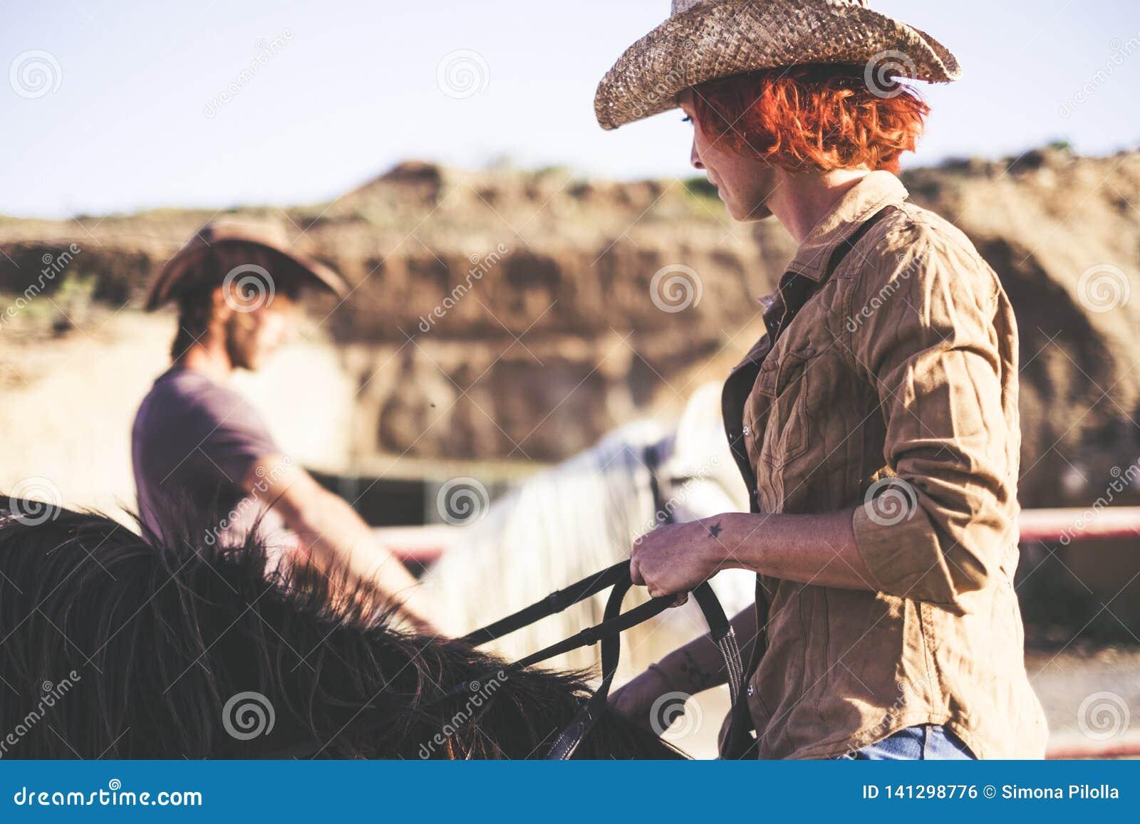 Para nowożytna kowbojska przejażdżka wpólnie jeden mężczyzna i jeden kobieta z dwa koniami grże filtrowego wizerunek dla alternat