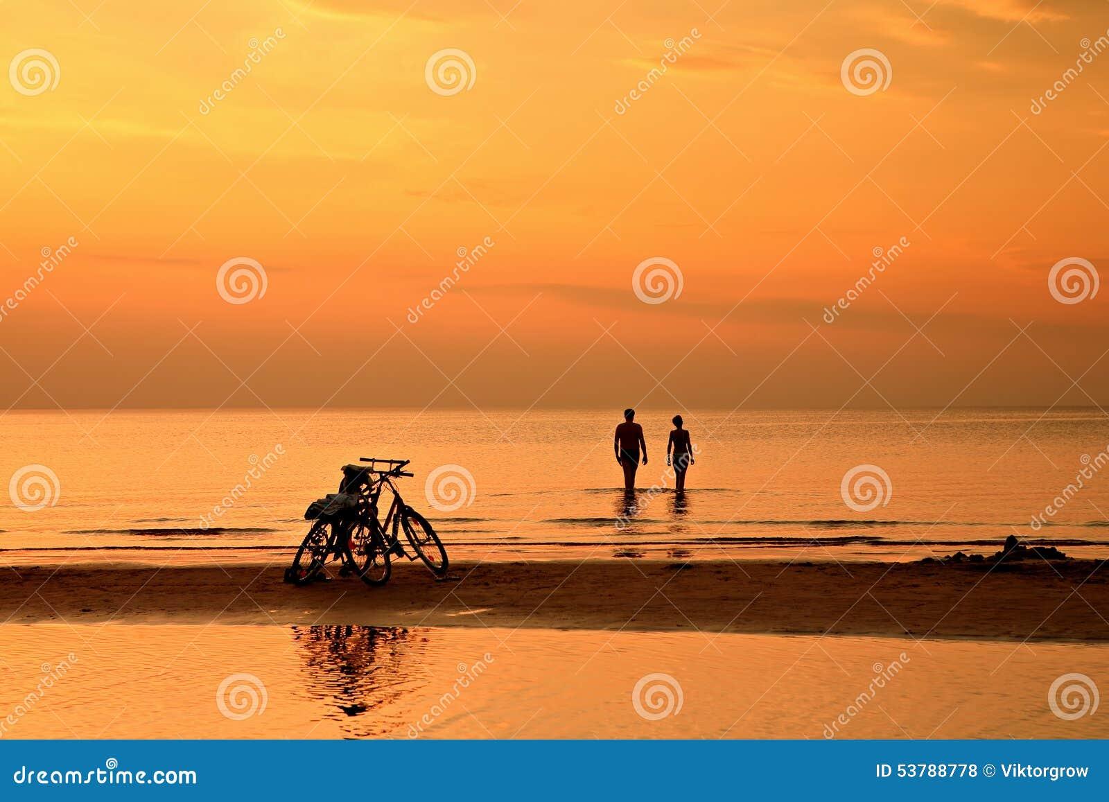 Para pływa w morzu przy zmierzchem na tle bic