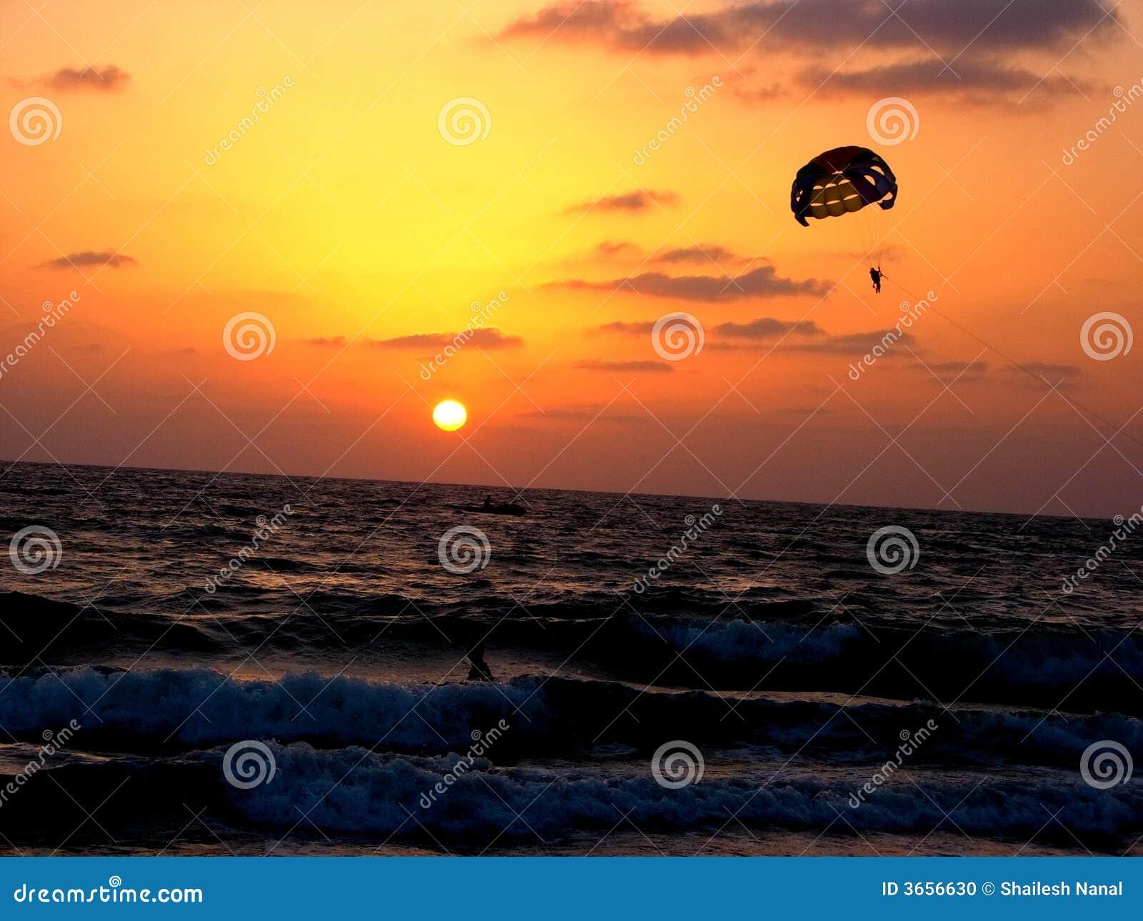 Para-sailing na praia no por do sol