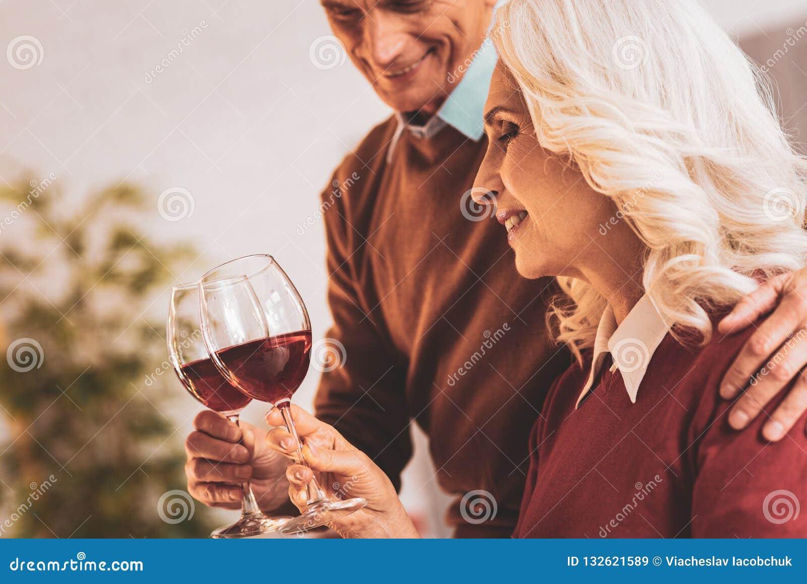 Para starzejący się ludzie cieszy się wino wieczór wpólnie