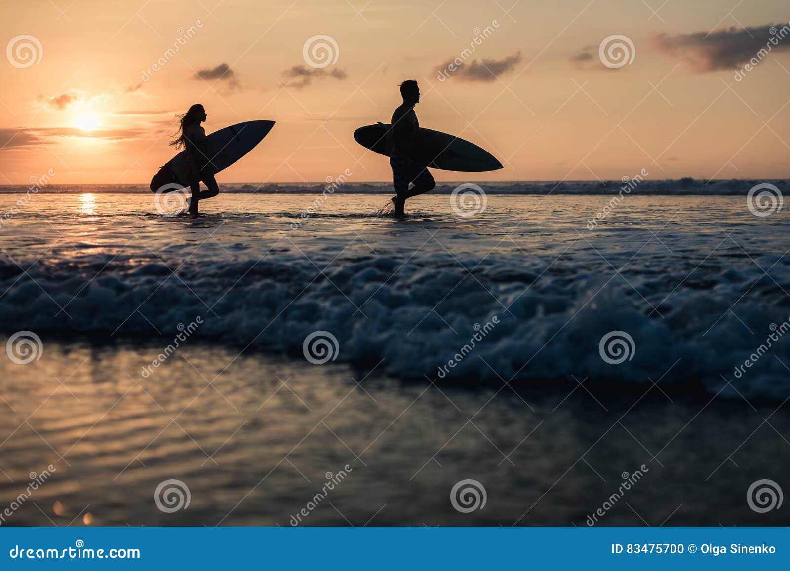 Para surfingowowie nad zmierzchem na linii brzegowej