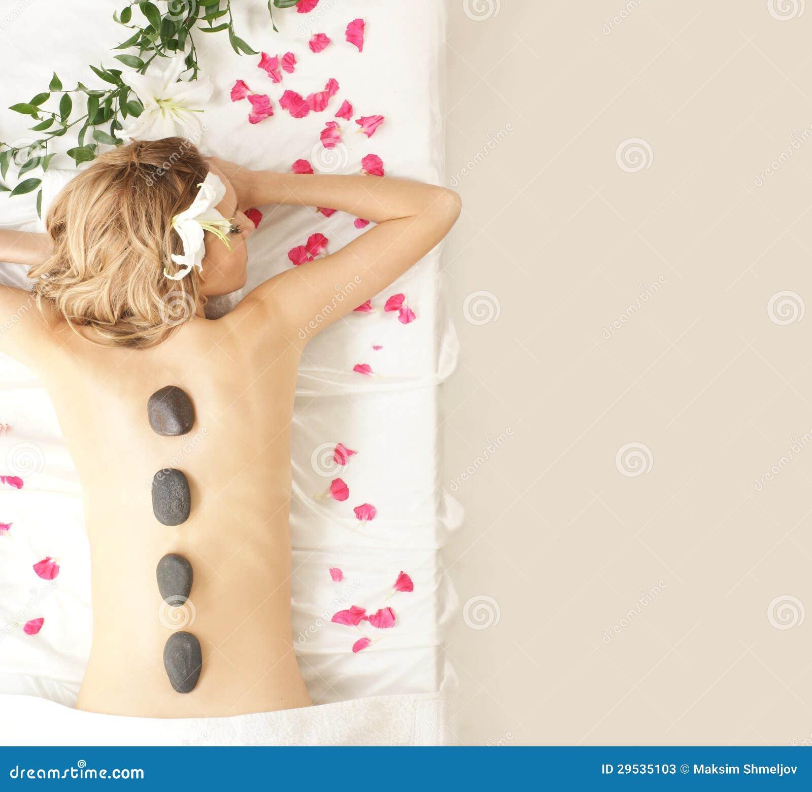 Para trás de uma jovem mulher em uma massagem da pedra da lava