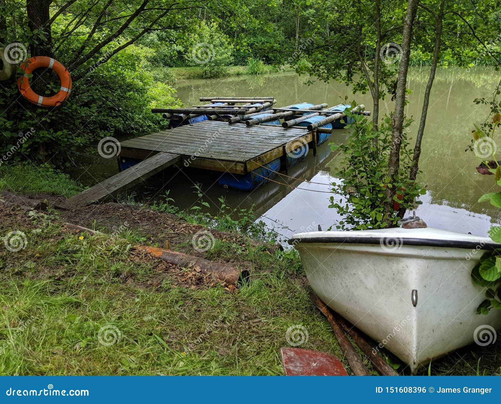 Para tratwy na pontonie z małą wioślarską łodzią na brzeg banku