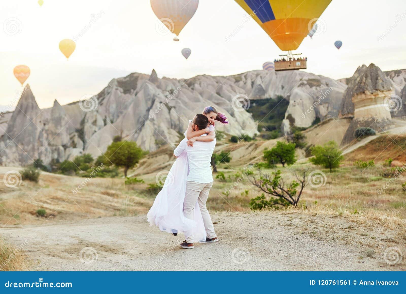 Para w miłość stojakach na tle balony w Cappadocia Obsługuje i kobieta na wzgórza spojrzeniu przy ogromną liczbą latanie balony