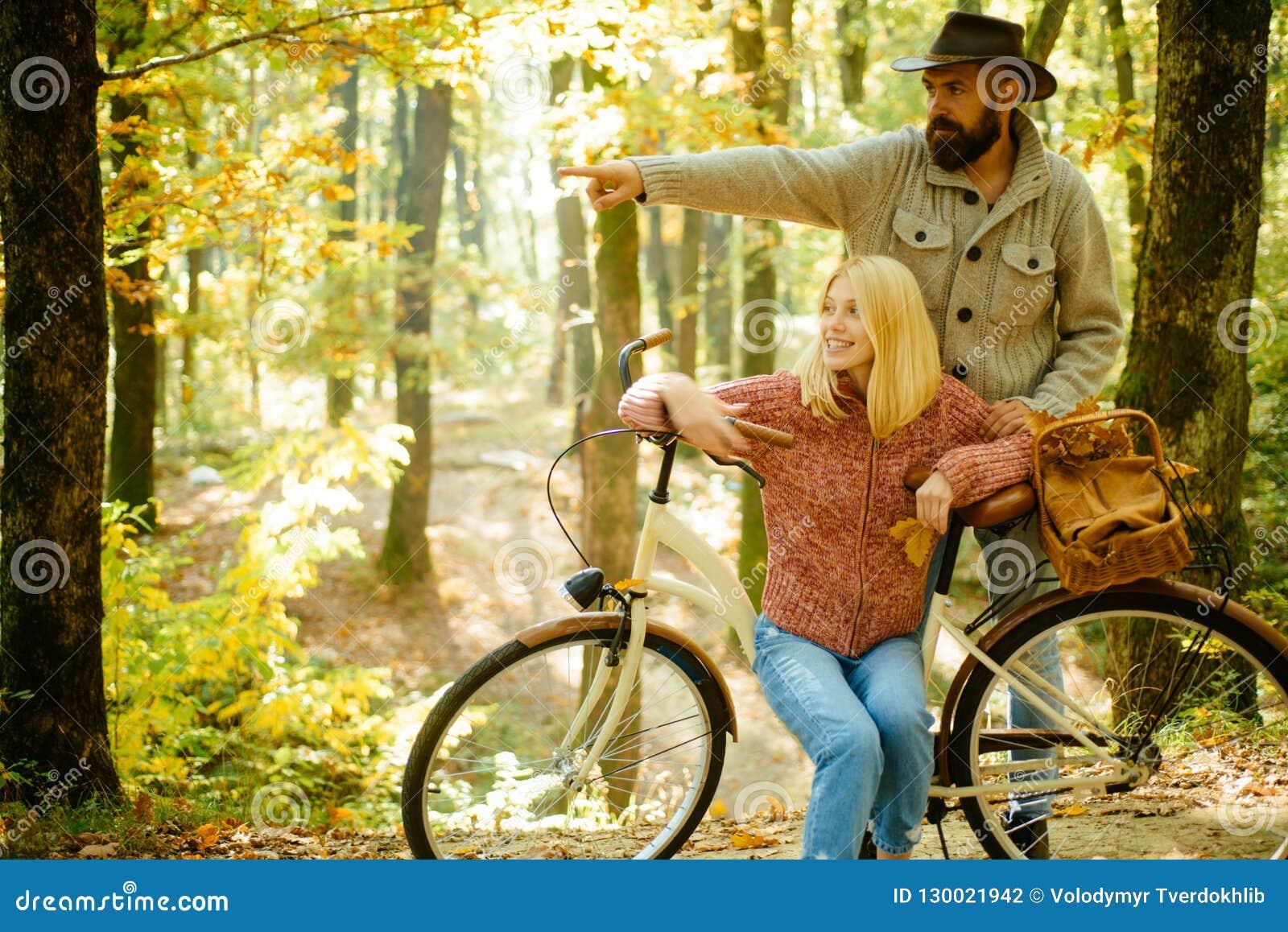 Para w miłości jedzie bicykl w parku Aktywni ludzie _ Jesieni para jest ubranym w jesieni odziewa