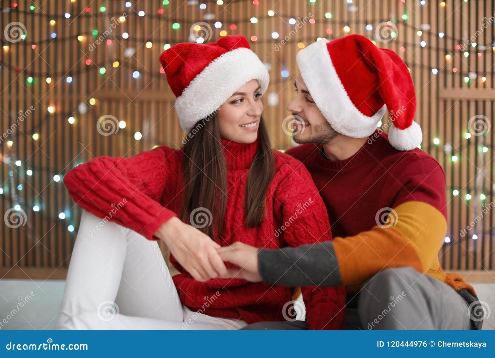 Para w Santa kapeluszach na zamazanym światła tle świętuje świętowania bożych narodzeń córki kapeluszy macierzysty Santa target27