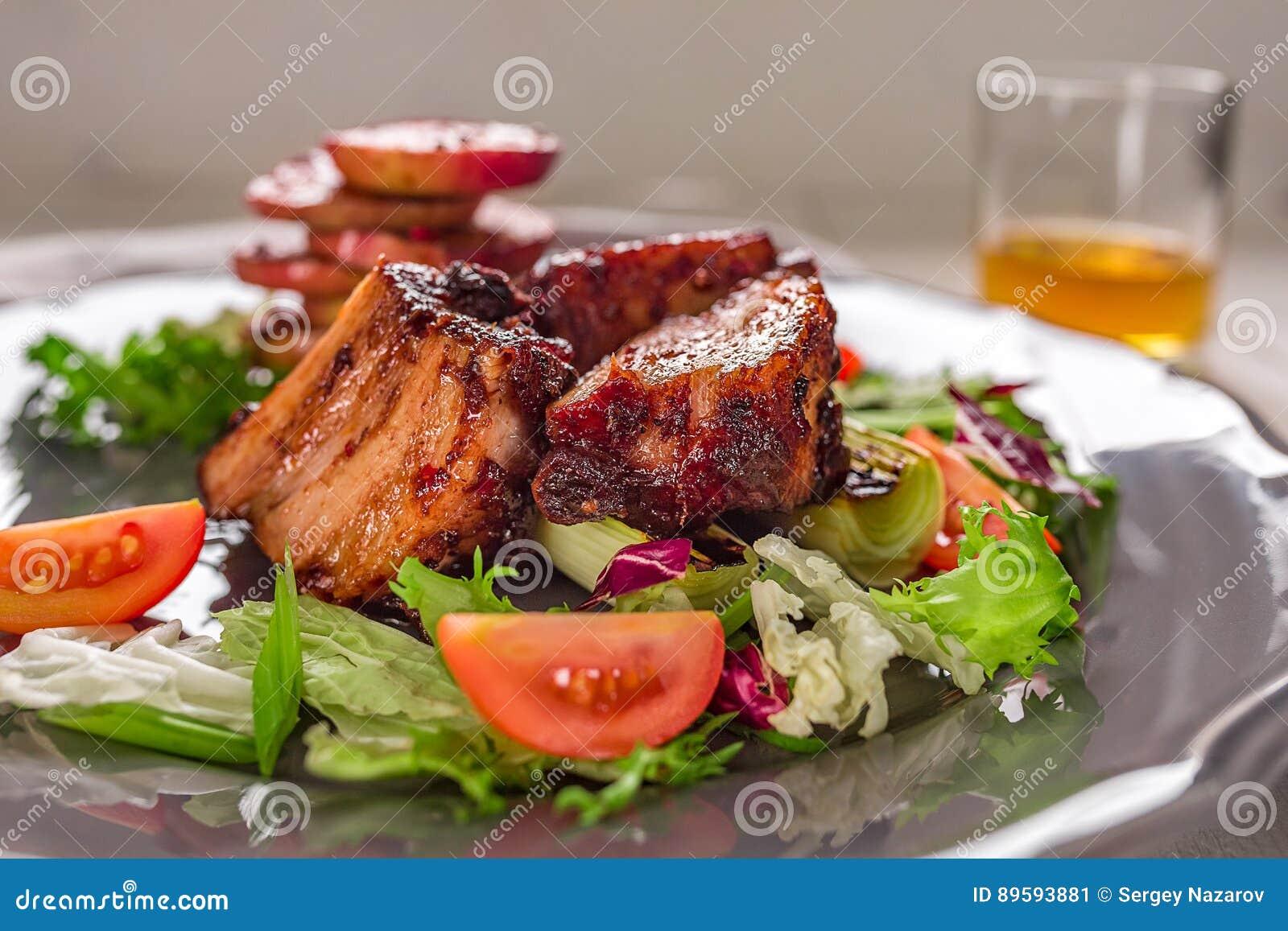 Paraboloïdes chauds de viande Les nervures de porc ont grillé avec de la salade et des pommes d un plat