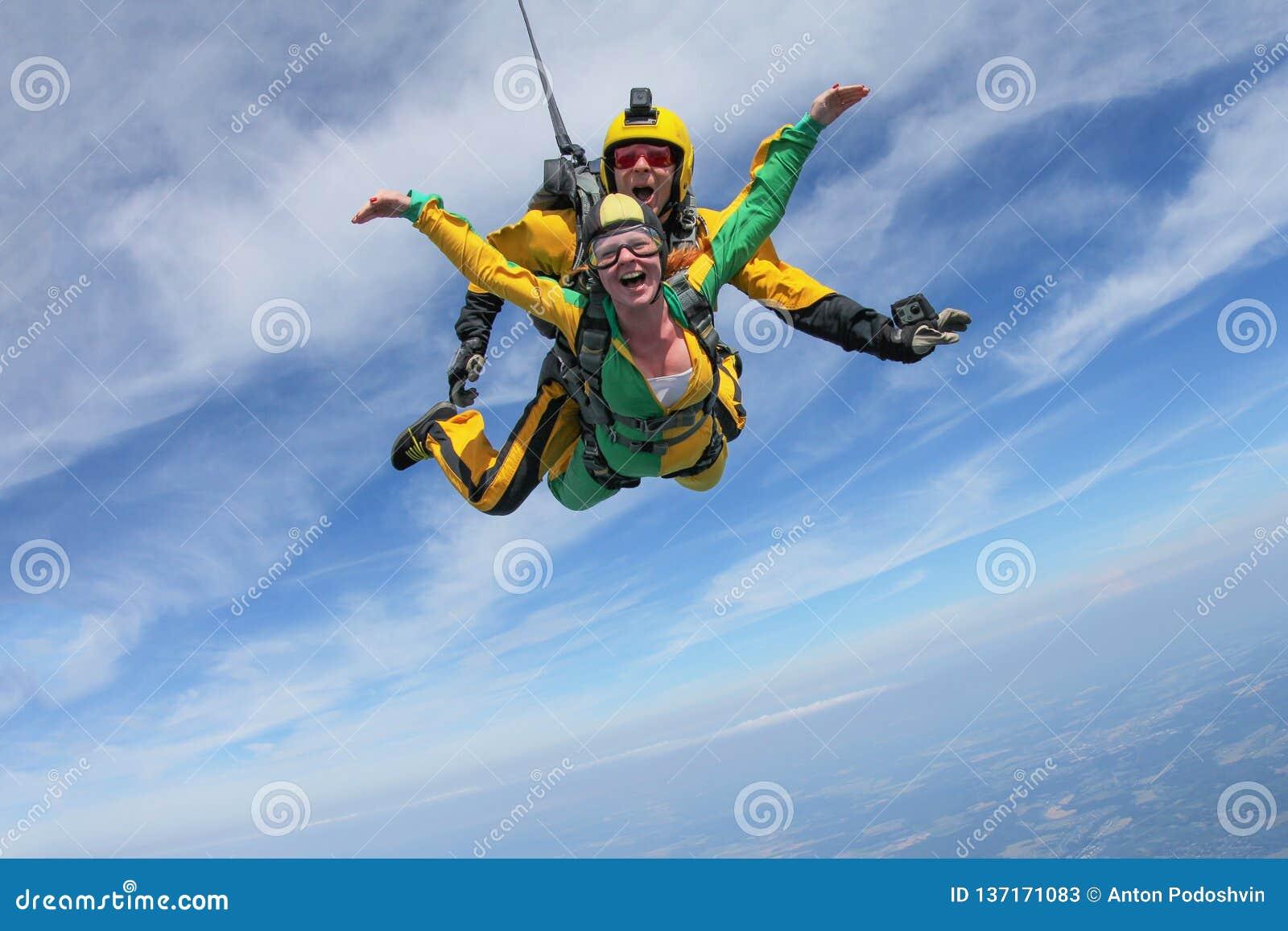 Parachutisme tandem Une fille active vole dans le ciel bleu
