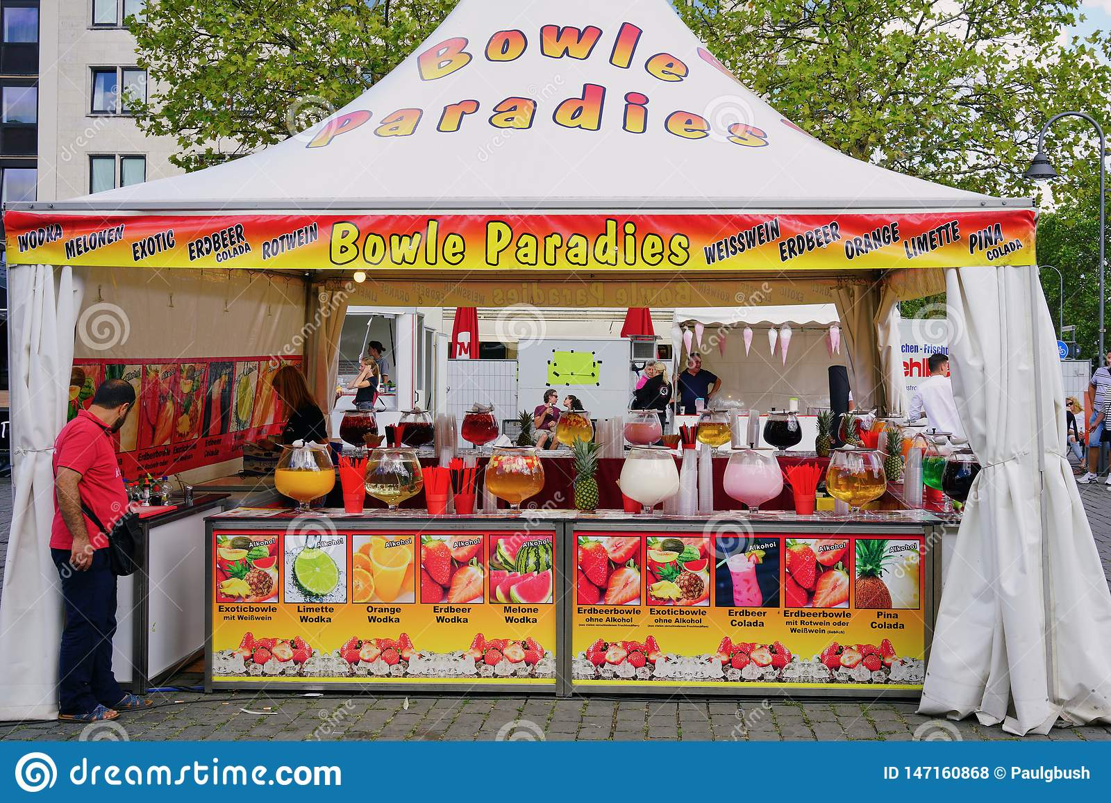 Parada del mercado de la ciudad que vende bebidas coloridas de la fruta y del alcohol