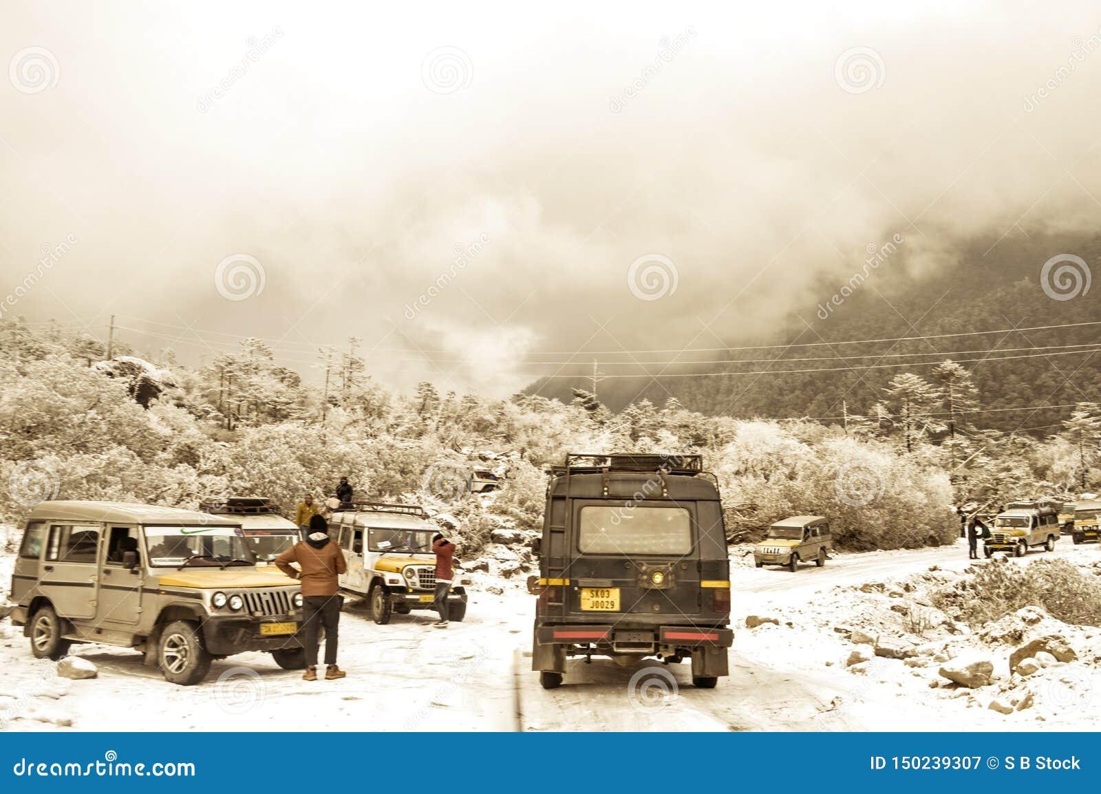 Parada do carro dos viajantes em uma estrada nevoenta do inverno Autoestrada nacional indiana com um carro que para perto na bord