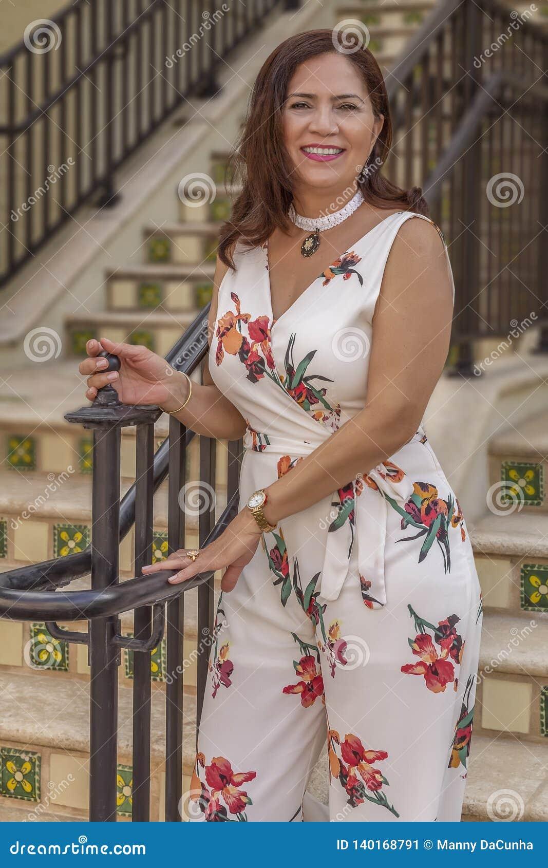 Paradas maduras de uma mulher do latino sofisticado na parte inferior das estrelas para uma foto op