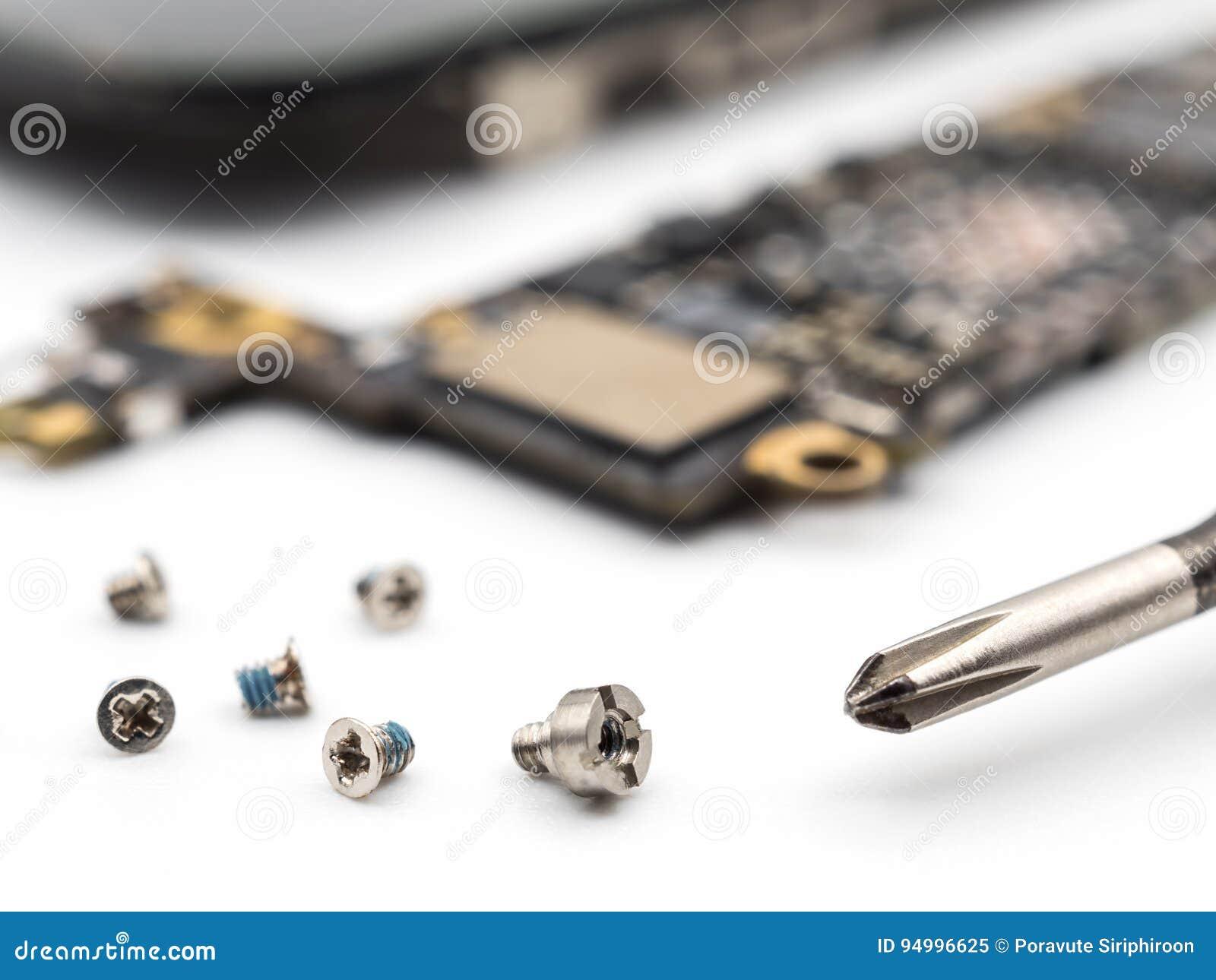 Parafuso e chave de fenda com componentes borrados do smartphone