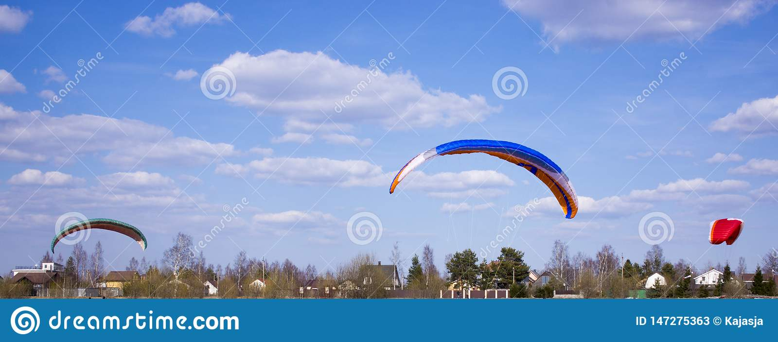 Paraglider flies against the backdrop of fields, land. View from above. Paragliding