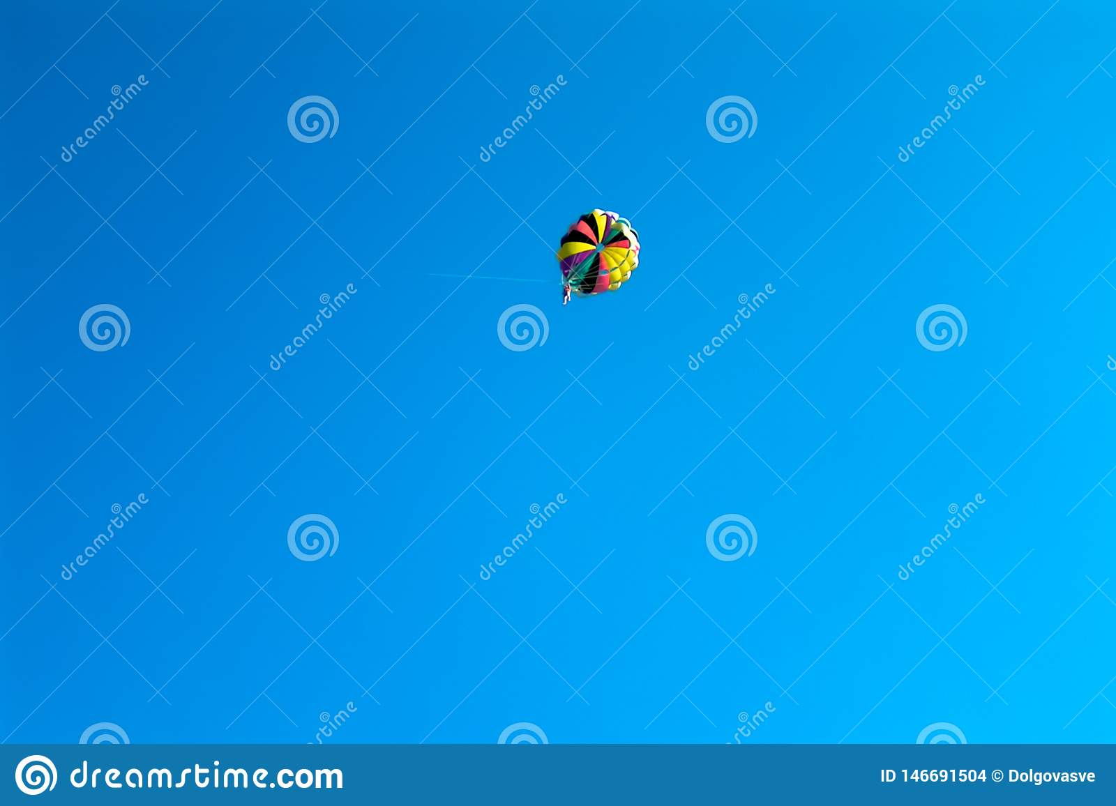 Skydiver flying on colored parachute in blue clear sky