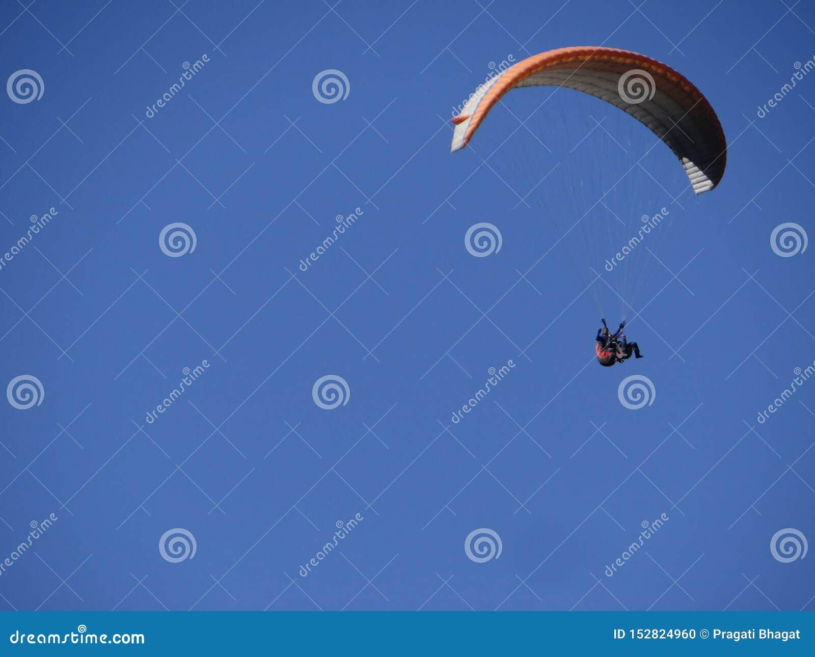 Paraglider jest latającym wysokością w w górę niebieskiego nieba w popołudniu i cieszyć się natury w swój prawdziwej jaźni